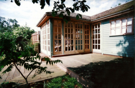 The finished summerhouse and darkroom, showing some of the tiered decking, leading down the garden.