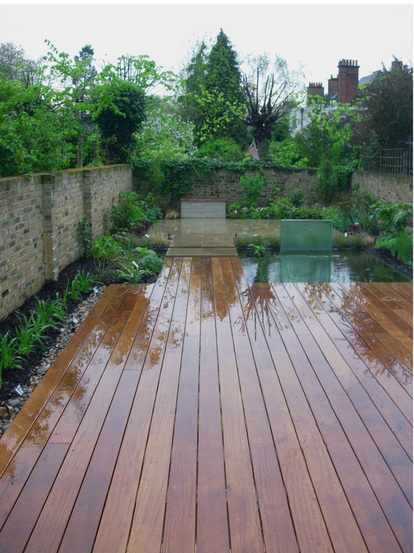 The new garden after planting, showing the Iroko deck, pond and glass water feature, as well as York stone paving.