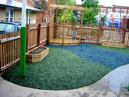 Reception play area showing raised beds, stage with pergola, and recycled rubber safety surface