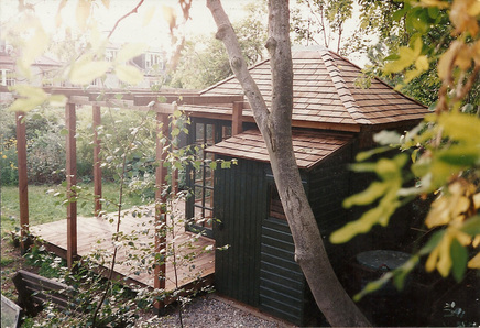 An attractive, small summer house with toolshed attached, deck and pergola